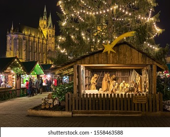 ERFURT, GERMANY - DECEMBER 13, 2018: Nativity scene at Christmas market on Domplatz in night. 14 wooden life sized figures are carved in Oberammergau. St Mary's Cathedral is visible in the background.