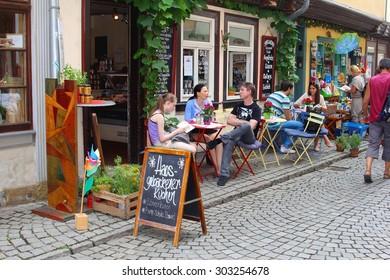 ERFURT, THURINGIA, GERMANY - August 7, 2017. Families and couples enjoy drinks at outdoor cafe terrace on Krämerbrücke (Merchants Bridge, Kraemerbruecke) ) in historic old town.