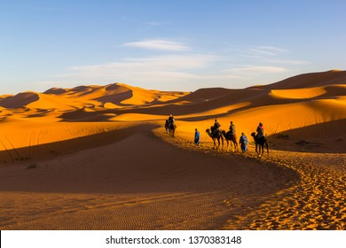Erg Chebbi, Morocco - February 24. 2019: Camel Riding Caravan along sand dunes at the sunset time in the Sahara Desert, Morocco