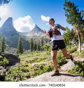 ERGAKI, RUSSIA - AUGUST 05 2017: Unknown girl sportswoman running through the mountains, participant in the trailrunning contest SKAYRANFEST August 5, 2017 in the national park Ergaki, Russia.