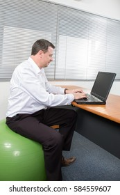 For an ergonomic office this businessman sitting on exercise ball at desk
