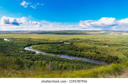 Ergun wetland in Inner Mongolia: the Ergune River flows through the Inner Mongolia steppe with many trees beside the river, and some clouds in the sky