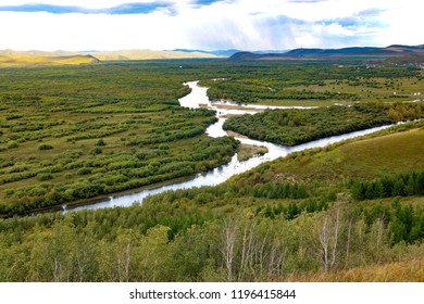 Ergun wetland in Inner Mongolia: the Ergune River flows through the Inner Mongolia steppe with many trees beside the river, some hills in the distance, and some clouds in the sky