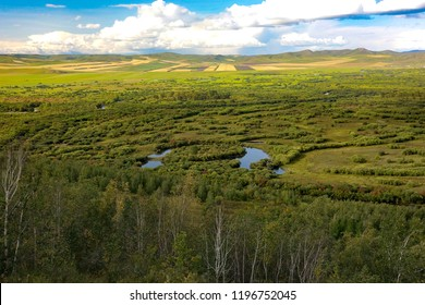 Ergun wetland in Inner Mongolia: a small island with the Ergune River around in the Inner Mongolia steppe with many trees beside the river, some hills in the distance, and some clouds in the sky