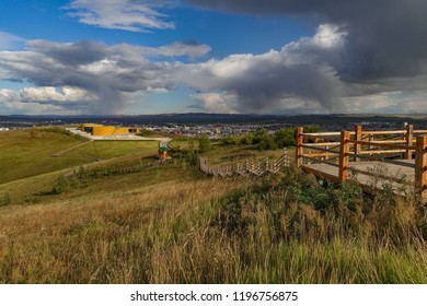 Ergun wetland in Inner Mongolia: wooden path towards a yellow house in the Inner Mongolia steppe, some hills and buildings in the distance, and some clouds in the sky