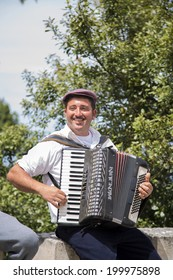 ERICE, ITALY - MAY 2, 2014: Unidentified accordion player play for the tourists at Erice. Erice is a wonderfully preserved mediaeval town 751m above sea level.