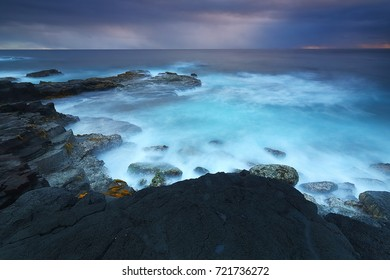 Erie, long-exposure image of waves crashing on the lava-rock strewn coast of the big island of Hawaii