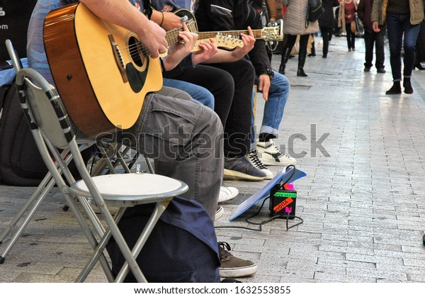 Ermou street Athens Greece-February 01 2020:A band of street musicians performing for the walking by peoples