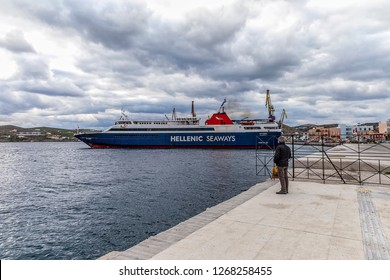 Ermoupolis: 27th December. Hellenic Seaways Ferry boat leaving Ermoupolis harbour. Man standing watching its deparchure. Ermoupolis, Syros, December 27th, 2018, Greece.