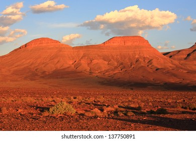 Eroded land under blue sky and white clouds at sunset, Atlas mountains, Morocco