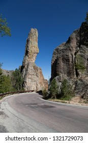 Eroded rock formations and trees stand tall against a clear blue spring sky next to Needles Highway in Custer State Park, South Dakota.