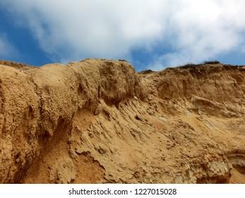 Eroded sandstone cliff rock formation against blue sky