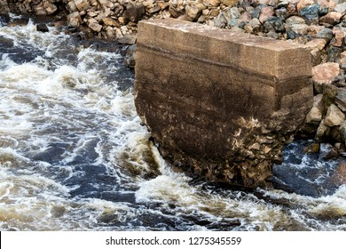 An eroded support for an old bridge. The bridge is gone, only the support remains. Erosion is severe.