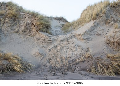 Erosion caused by waves and people on a sand dune in winter