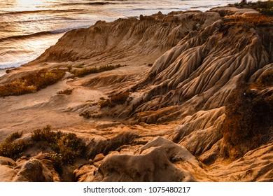 Erosion of ocean side cliffs at sunset