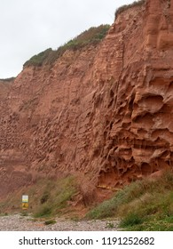 Erosion in the red sandstone coastal cliffs at Budleigh Salterton, Devon, UK and the start of the deserted nudist beach.