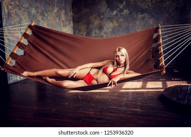 erotic blonde lying on hammock in charming red lingerie indoors
