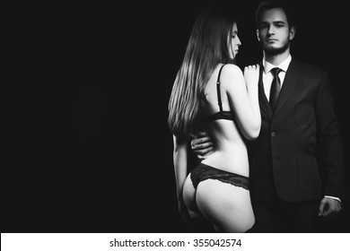 Erotic concept of woman in underwear next to men in suit. Sensulity and sexuality. Erotica and fetish. Black and white image
