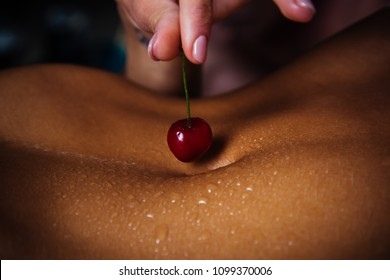 Erotic dessert. Seductive cherry on the female navel. The female hand holds a cherry for temptation. A beautiful young female body and delicious food before sex. Beautiful woman and enjoy life