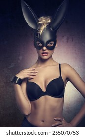 erotic easter dark portrait of very sexy blonde female with curly hair-style and black lingerie, wearing bizarre dark bunny mask on the face and looking in camera
