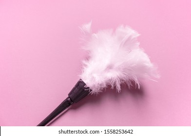 Erotic feathers. Tickling body sensation. Role-playing maid costume. White feathers pink background.