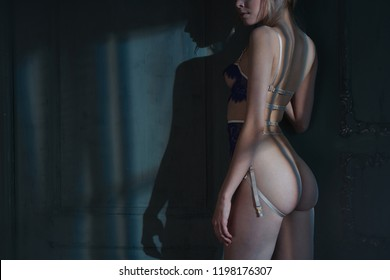 Erotic figure of young beautiful woman in sexy lingerie. Pretty model with sexy figure shows her body in interior. Blue female panties. Lifestyle photo.