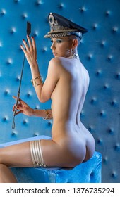 Erotic girl in a military cap and with a whip in her hand