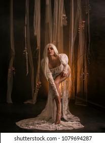 erotic goddess  Banshee Pale blonde model. white vintage dress. Seductive princess, sexy naked nude long tan legs posing  backdrop fabulous gothic fairytale room pieces  veil fabric. Mary Magdalene