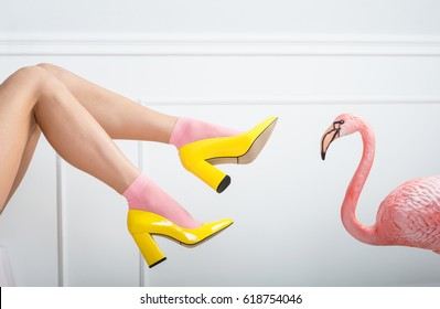 Erotic legs in pink socks and yellow shoes. Young sexy female legs on a white background
