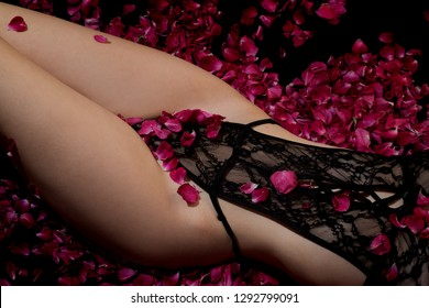 Erotic lingerie. The girl in the roses. Bed for Valentine's Day. Beautiful slim girl lying in black lace. Female shape. Seductive Hips. Woman waist.