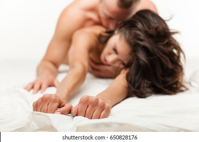 Erotic play. Fashion. Couple in love. Young sexy couple in love lying in bed in hotel, embracing on white sheets, close up legs, romantic mood. Good morning. Love story. Sexual concept. Life. Freedom