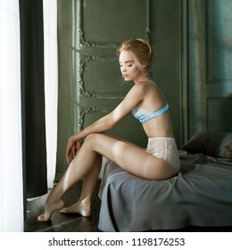 erotic portrait of young beautiful woman in sexy lingerie. Pretty blonde with sexy figure shows her body in interior. Blue female panties. Lifestyle photo.