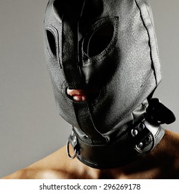 Erotic style image with a men wearing a leather mask or hood over his head