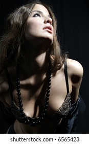 an erotic woman with bra and pearl necklet