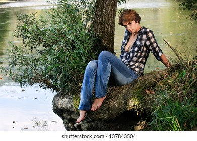 Erotic young woman wet clothes sitting by the river