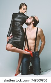 Erotica and fashion concept. Man and pretty girl with seductive faces on grey background. Sexy couple in love with half naked bodies. Macho stands on knees near sexi woman in red high heeled shoes