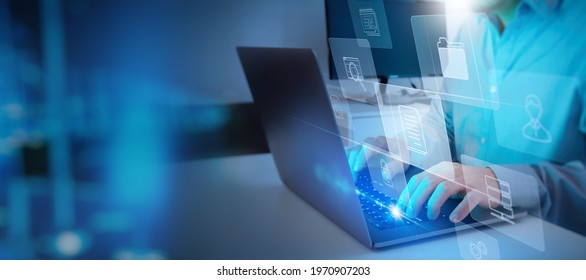 ERP, document management concept.Businessman working with laptop computer with icons on virtual screen and office blur background.