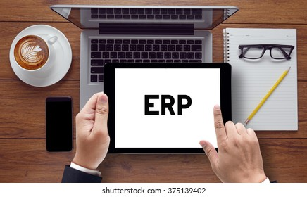 ERP message on tablet pc screen held by businessman hands - concept, top view computer, phone ,coffee, Warm tone