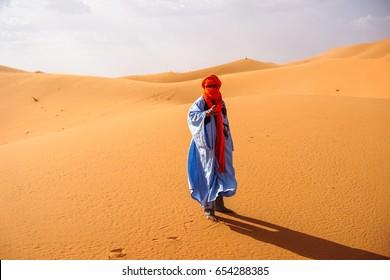 Errachidia, Morocco March 20, 2017. Berber Man in Traditional Clothes walking among  Sahara Desert, Morocco