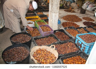 ERRACHIDIA, MOROCCO - MAY 5, 2013: A Moroccan seller selling various types of dates On local market in Errachidia