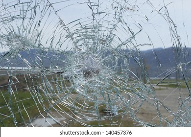 An errant rock has shattered glass/Shattered Glass/A vandalized window after someone has tossed a rock.