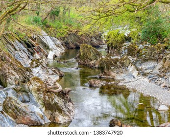 Erroded rocks of all shapes, sizes and colour in the  River Mawddach as it passes through a Welsh woodland.