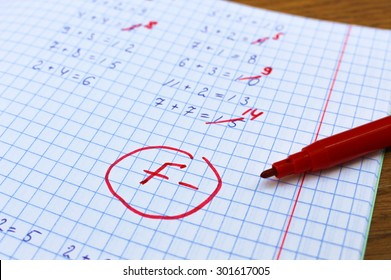 Errors corrected in red pen in a notebook. Bad score for the solution of mathematical expressions. Mark F-.