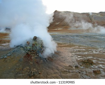erupting geyser of steam with sulfur deposits, Iceland