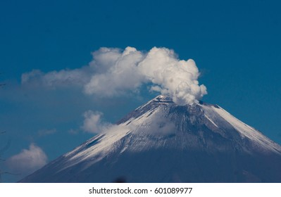 Erupting volcano with snow and blue sky background