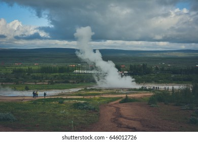 Eruption of Strokkur geyser in Iceland in summer with many tourists in the background - vintage colors with some grain