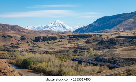 Erzincan, Turkey - August 2018: View of a valley with a train and railway with snow capped mountains and Firat river near Erzincan, Turkey