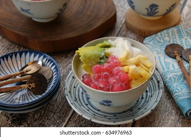 Es Oyen Bandung. Popular iced dessert from Bandung, consists of coconut, jackfruit, tapioca pearls, and avocado in sweetened coconut milk. Served in a ceramic bowl on a rustic wooden table.
