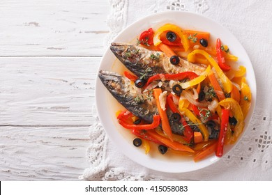 Escabeche fish: mackerel in vegetable marinade close-up on a plate on the table. horizontal view from above
