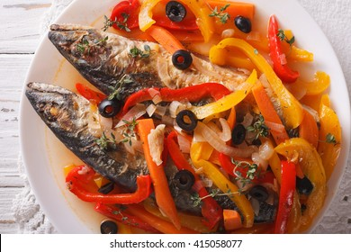 Escabeche of mackerel fish with vegetables close-up on a plate on the table. horizontal view from above